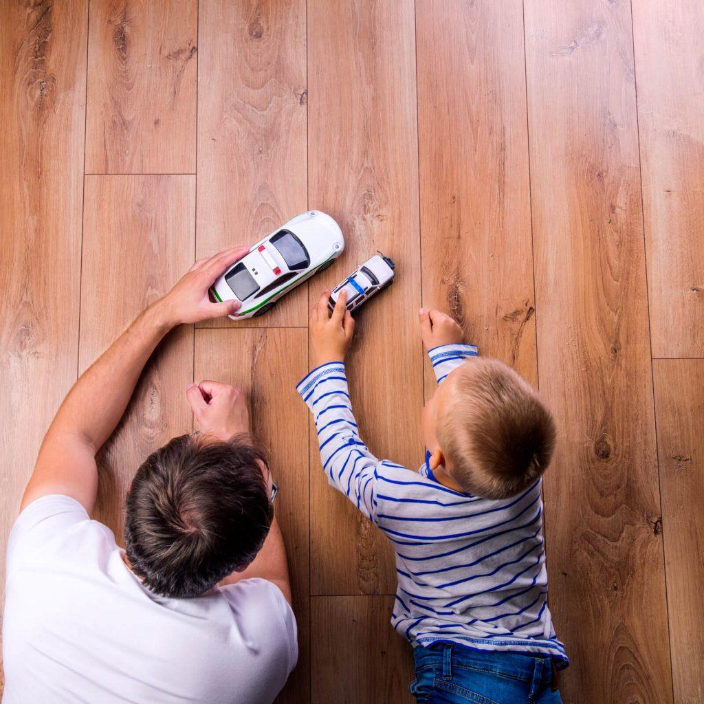 Kid and father playing on Hardwood floor   Everlast Floors